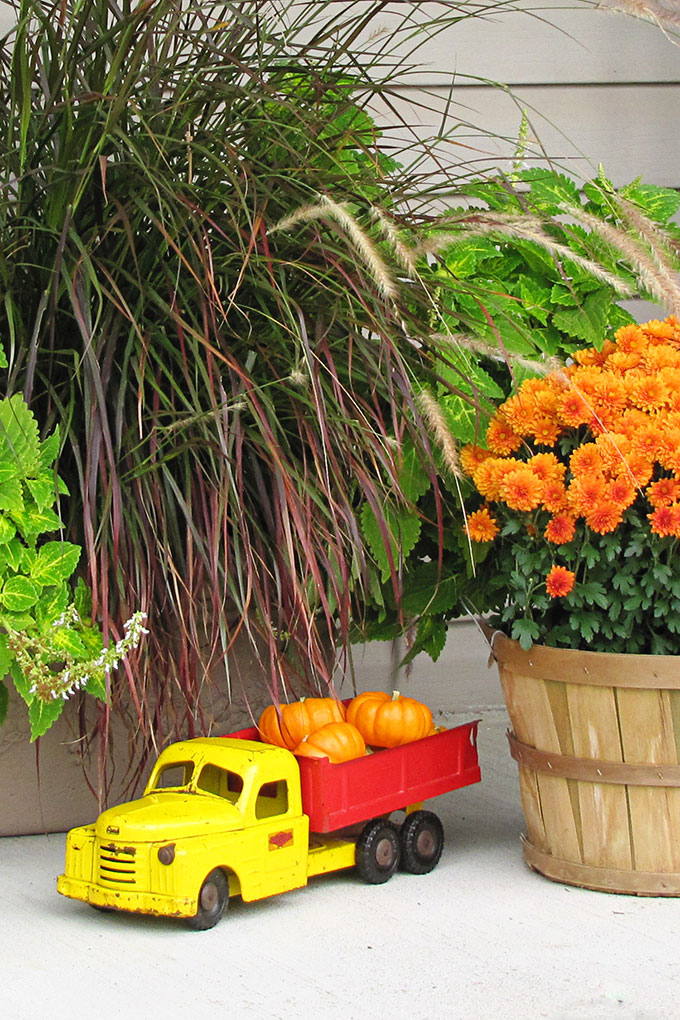 LOTS of fall porch ideas and inspiration including this vintage toy truck hauling pumpkins. Your porch is the first impression people get of your home, so make it a festive one! Whether you love traditional, farmhouse or eclectic decor you'll find inspiration through this girl's festive and unique look back at her fall porch decor over the years!