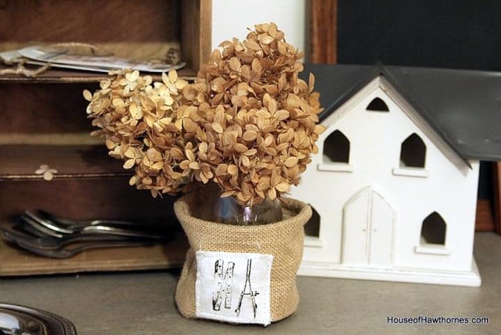Dried hydrangeas displayed in a burlap vase.
