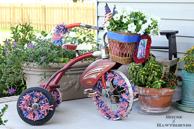 A vintage little red Tricycle decorated for the 4th of July with patriotic crepe papers, flags and flowers.  A cute DIY project for patriotic porch decor.