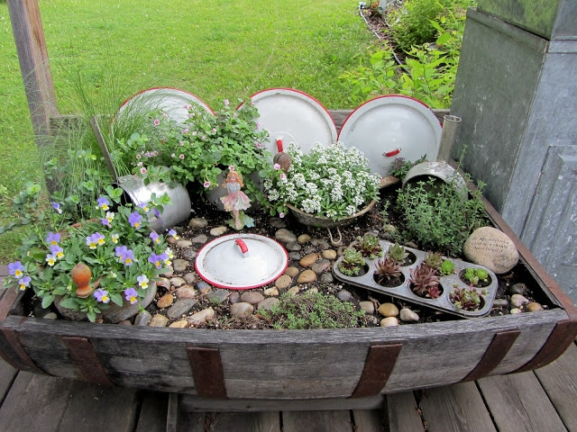 Fairy garden in a wine barrel from organizedclutter.net