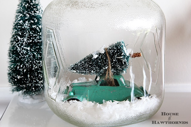 Car with Christmas tree tied to top in a snow jar