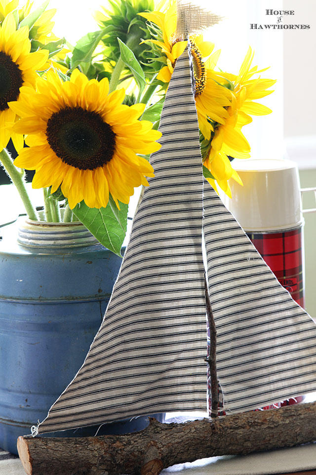 Sunflower vignette using vintage picnic jug, thermoses and twig sailboat