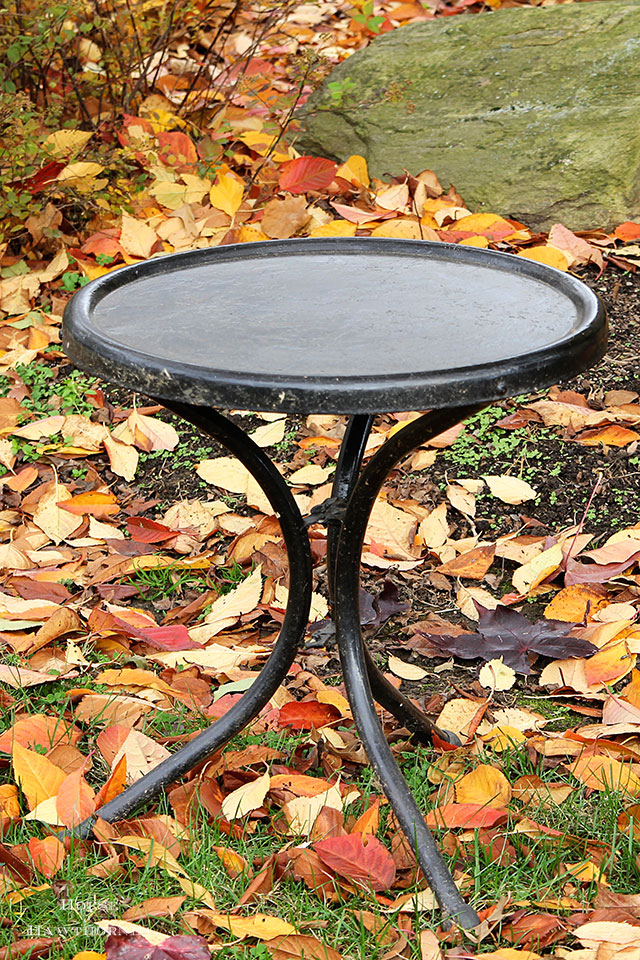 Vintage black metal table that is part of a motel chair set