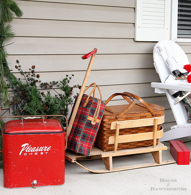 Fun holiday front porch ideas are shown, including chalk painted skis, vintage Thermoses and plaid decor for Christmas.  And most of the items were found at thrift stores and estate sales.