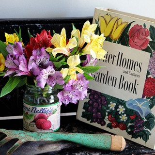 Vintage style garden decorating in the entryway, including vintage garden planters, gardening tools and colorful retro Better Homes and Gardens Garden Book.