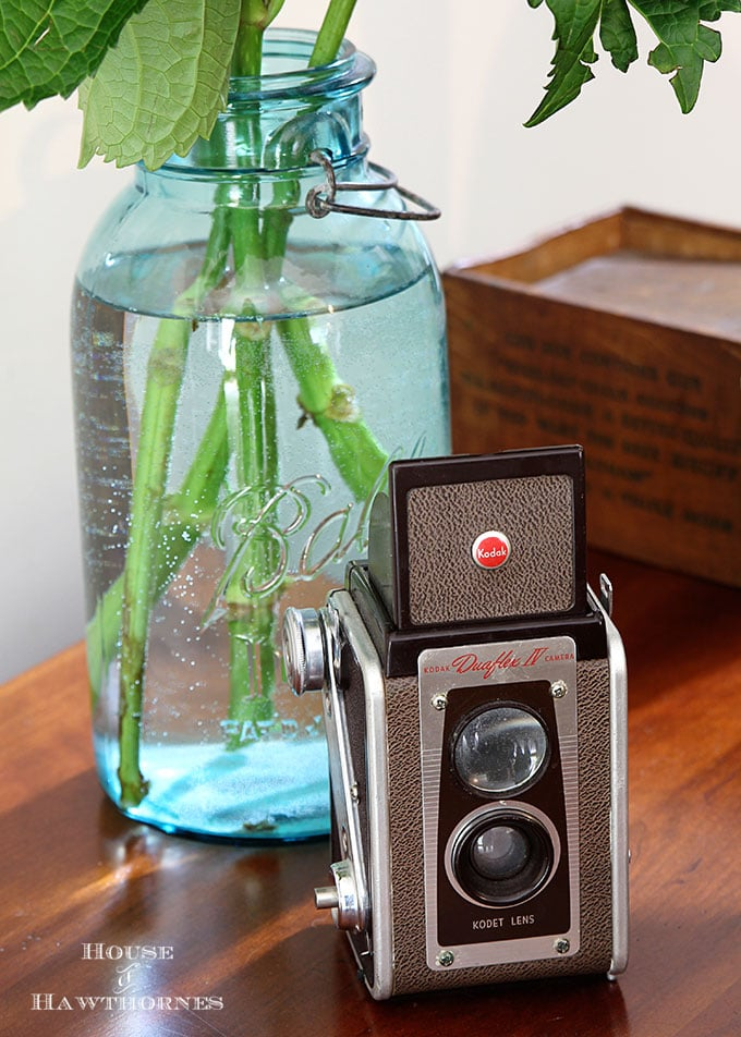 A vintage Kodak Duaflex IV camera as part of a rustic vintage eclectic style summer home decor tour including vintage thermoses, cameras, typewriter and vintage croquet and badminton equipment.