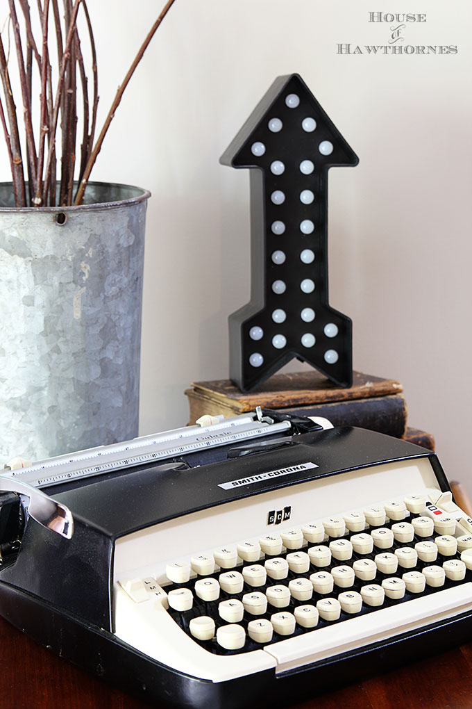 Vintage Smith Corona Galaxie typewriter as part of a rustic vintage eclectic style summer home decor tour including vintage thermoses, cameras, typewriter and vintage croquet and badminton equipment.