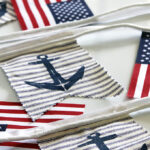 A super easy DIY patriotic banner tutorial. Anchors, flags and sailboats combine for a nautical Fourth Of July home decor style or any patriotic holiday.