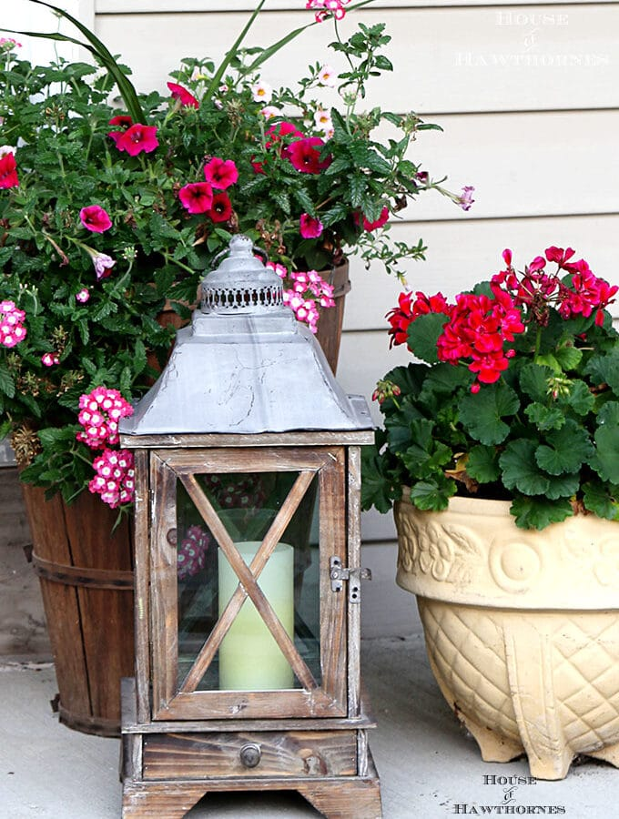 Summer porch decorating ideas and inspiration using farmhouse touches, vintage items, plenty of annual flowers and a healthy dose of patriotic decor.