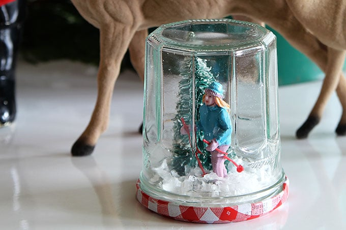 Learn how to make a super cute DIY snow globe from a jelly jar. A quick, easy and inexpensive holiday craft project the kids can help with.