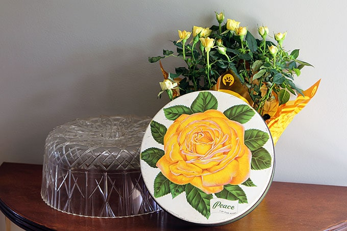 Vintage rose candy tin and mid-century plastic cake cover - could be lucite or acrylic