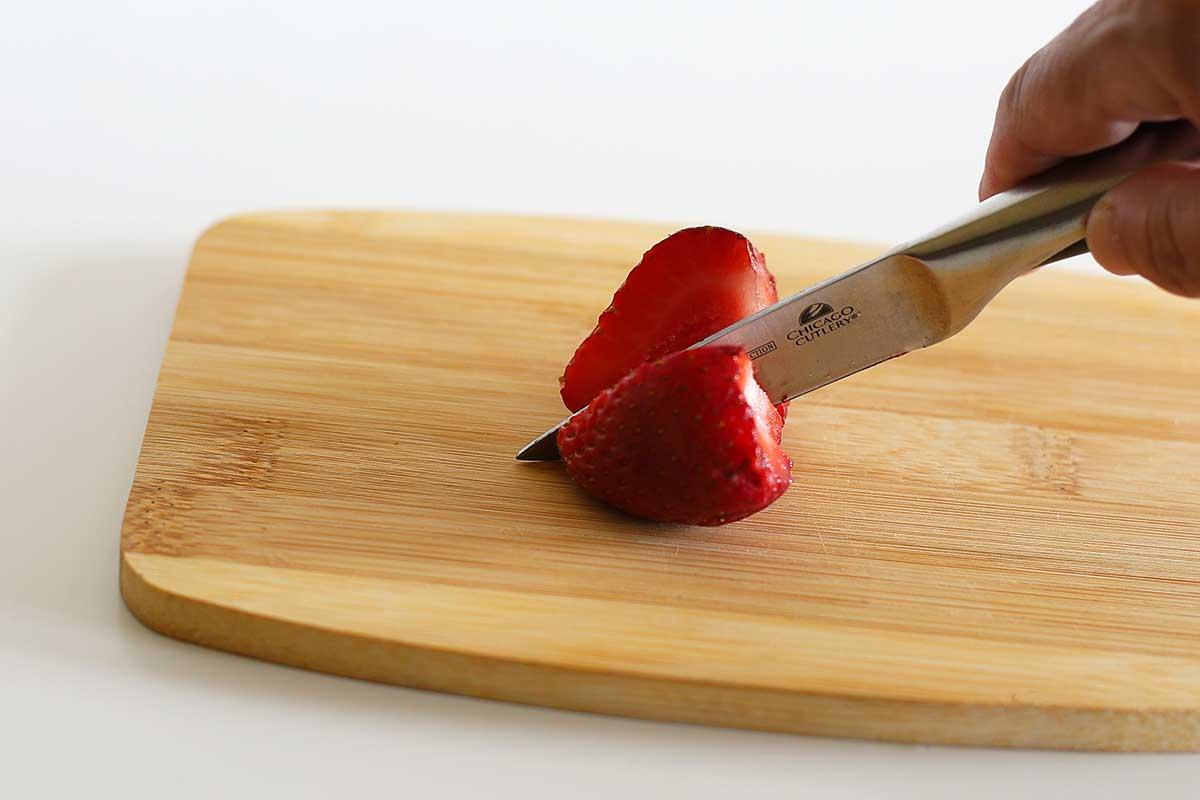 Cutting strawberries in half.