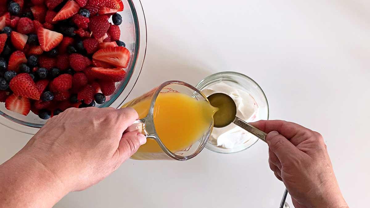 Pouring orange juice into sour cream.