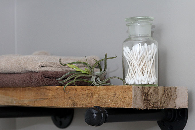 DIY industrial pipe shelving in bathroom topped with air plant, towels, and q-tips
