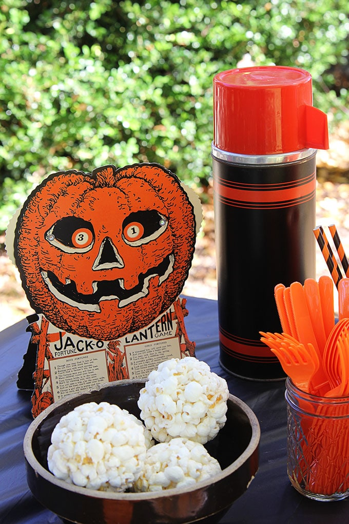 Beistle Halloween Game at a traditional Halloween party with orange and black decor including blow molds and vintage inspired Halloween decorations.