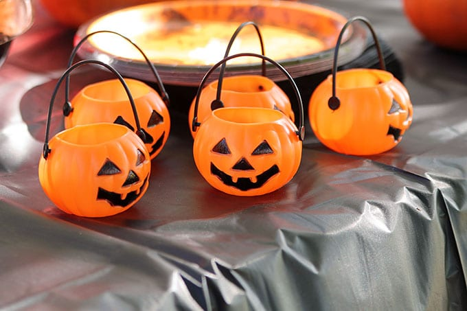 Plastic Halloween pumpkin candy containers at a traditional Halloween party with orange and black decor including blow molds and vintage inspired Halloween decorations.