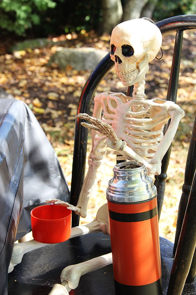 Skeleton at a traditional Halloween party with orange and black decor including blow molds and vintage inspired Halloween decorations.