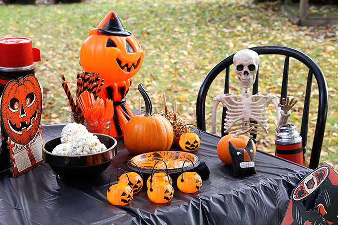 A traditional Halloween party with orange and black decor including blow molds and vintage inspired Halloween decorations.