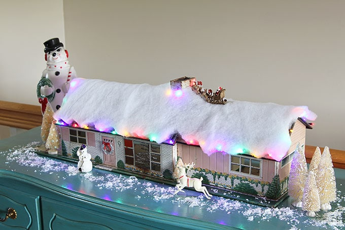 A mid-century modern Christmas dollhouse complete with a tiny little tinsel Christmas tree and Santa on the rooftop.