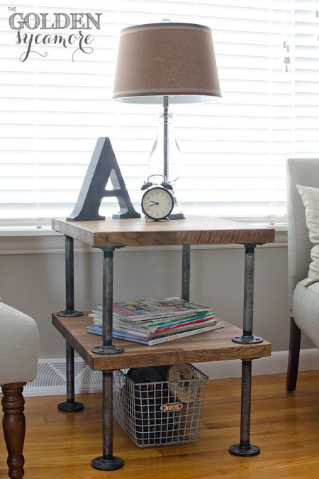Industrial pipe side table styled with magazines, a lamp and a clock