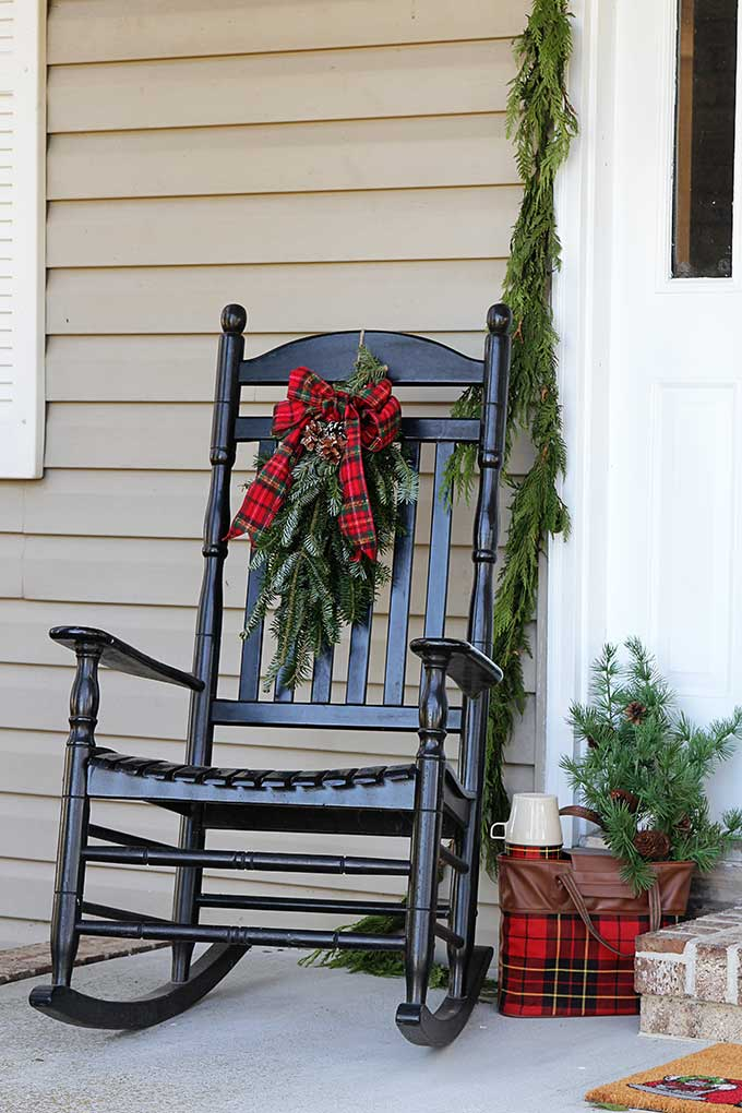 Traditional black porch rocker on a Christmas porch