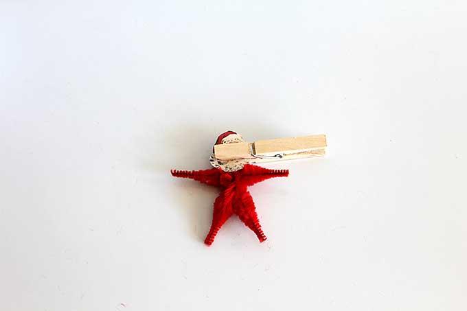 Using clothespin to glue head to pipe cleaner Christmas ornament