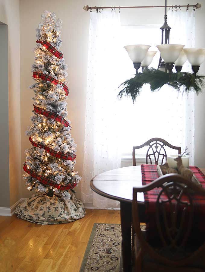 skinny flocked tree in a vintage rustic christmas dining room
