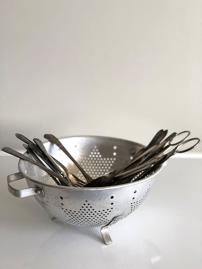 Colander and silverware to make wind chimes