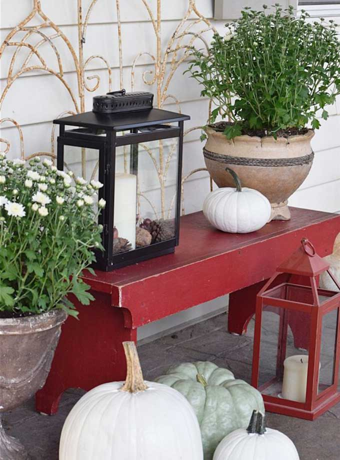 Red bench mixed with heirloom pumpkins and lanterns for outdoor fall decor from Timeless Creations.