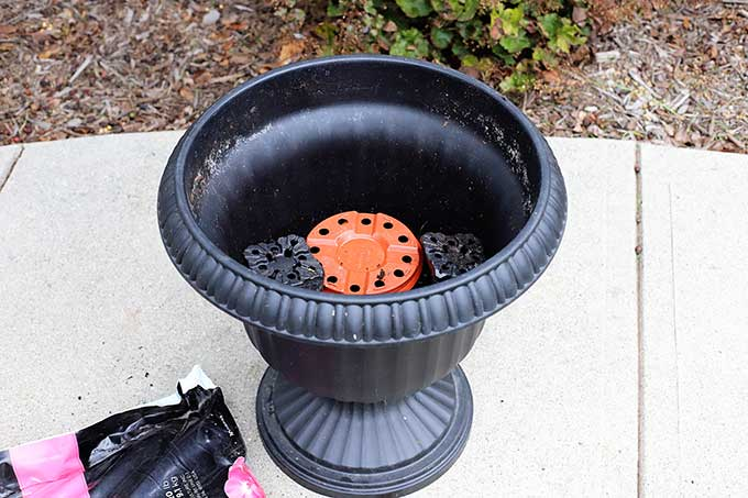 Filling urn with potting soil.