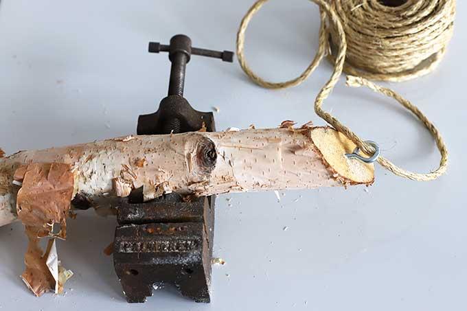 Attaching eye hook to log bird feeder