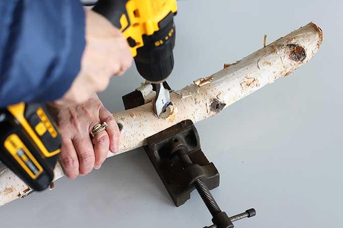 Drilling holes in log bird feeder