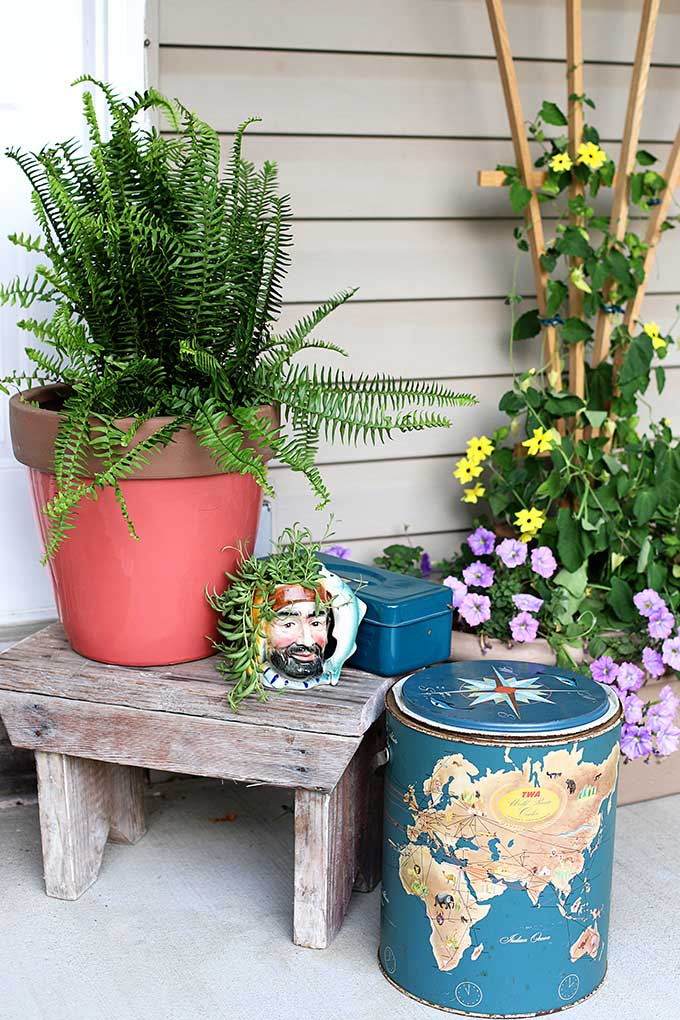 Boho styled summer porch decor using thrift store mug as a planter and vintage cooler as decor
