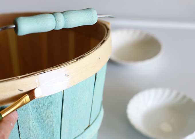 Painting wooden bushel basket.