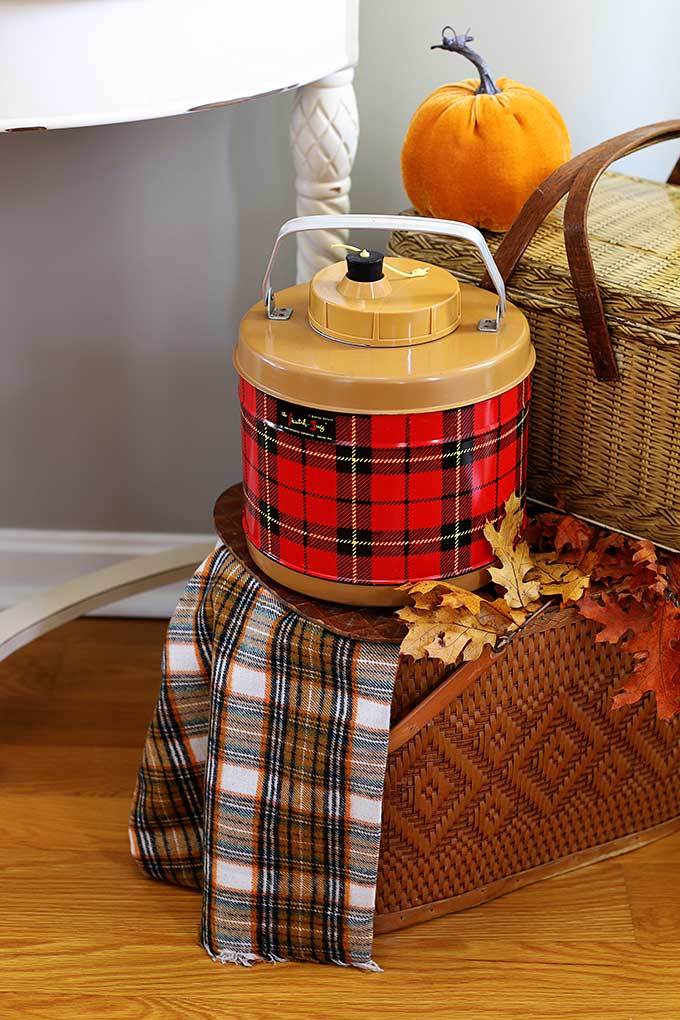 Vintage thermos and picnic basket used as fall decor