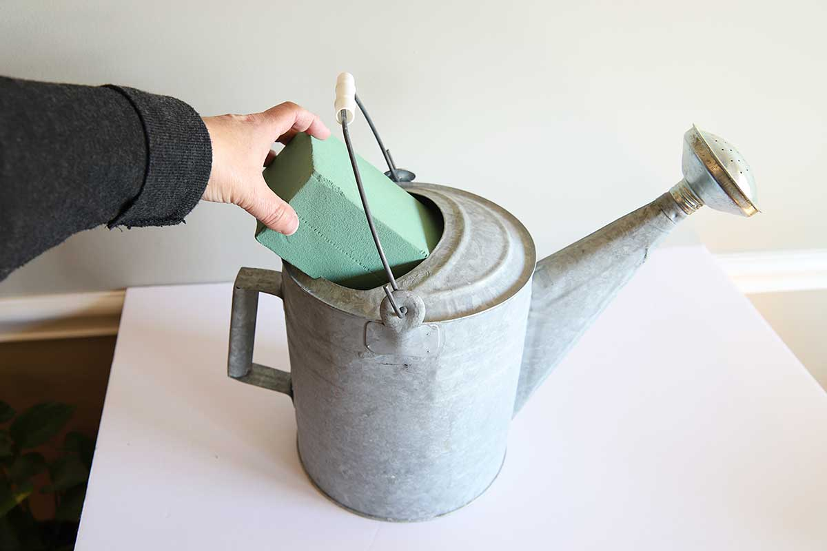 Adding floral foam to watering can