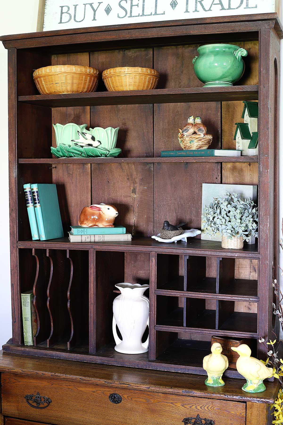 adding spring decor on the bookshelf
