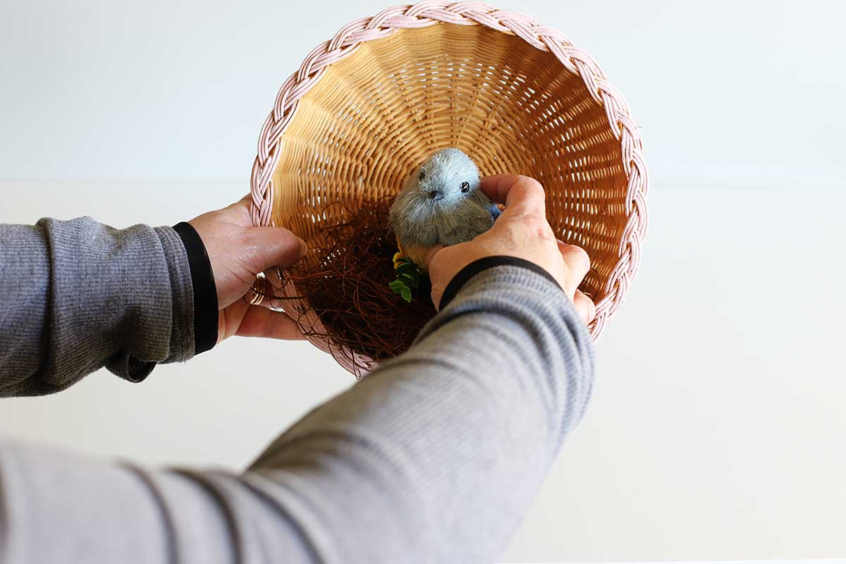 gluing bird to decorative nest