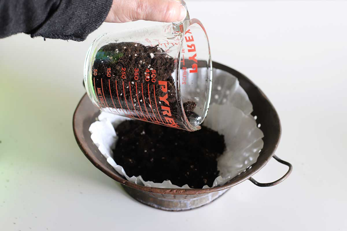 adding dirt to colander planter