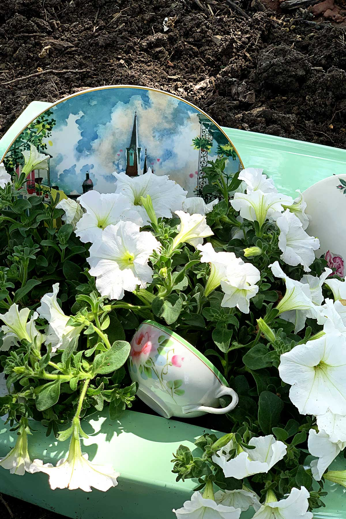 dishes and flower soap bubbles in repurposed sink turned into garden planter