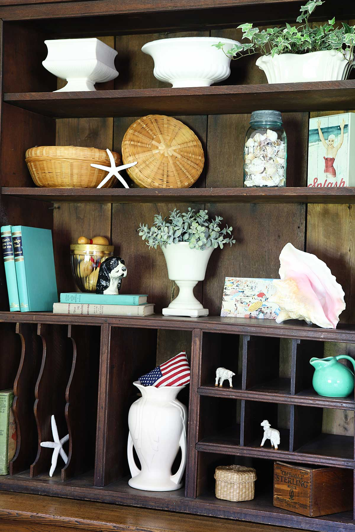 bookcase shelves decorated for summer with shells and beach theme