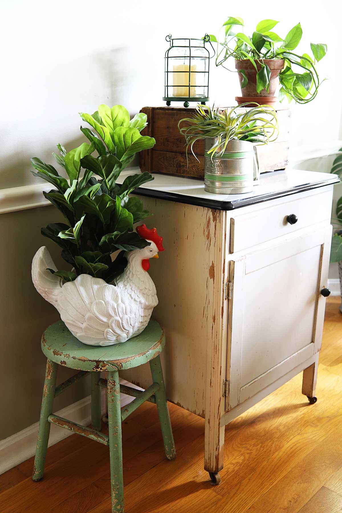 farmhouse vignette using vintage kitchen cabinet with enamel top