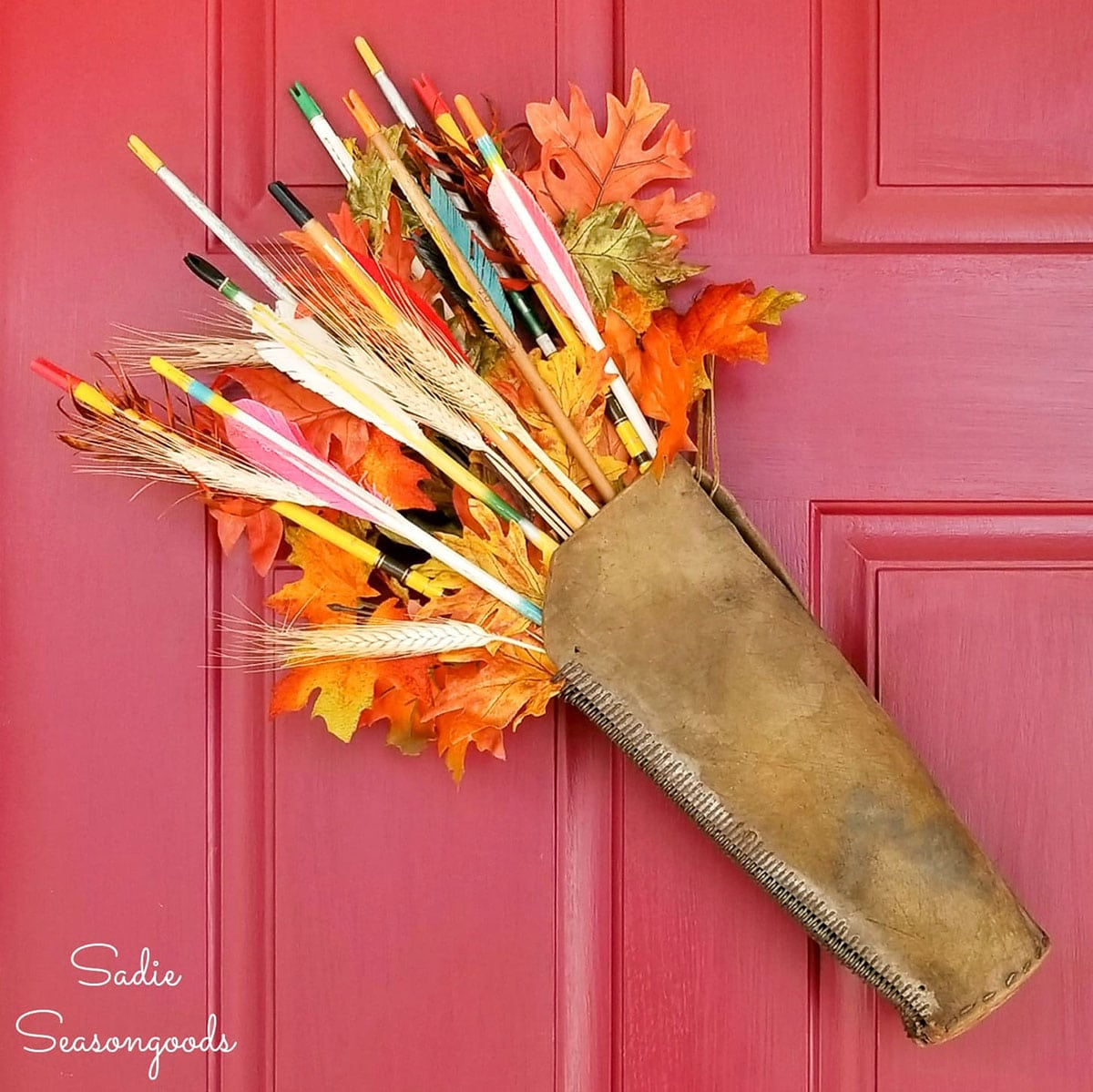 quiver of arrows hung on red door as fall wreath