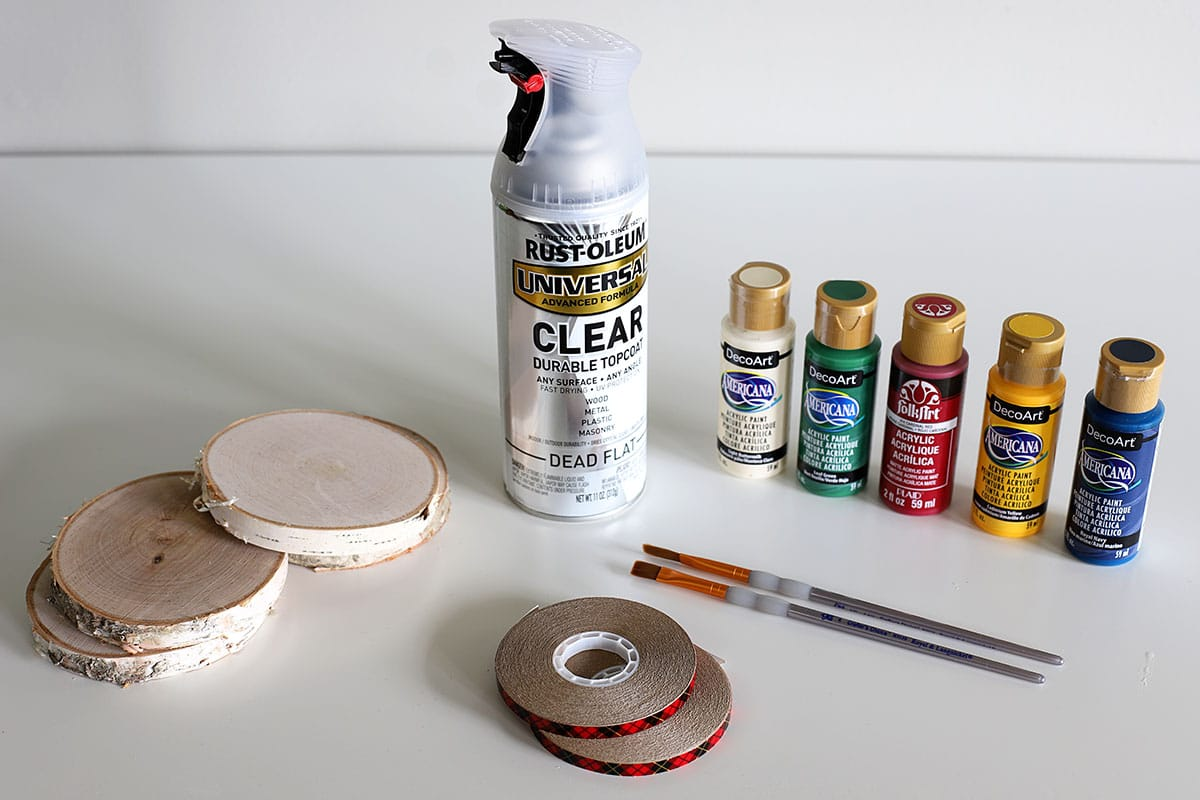 supplies needed for making coasters - wood slices, craft paint, paint brushes, sealer and tape