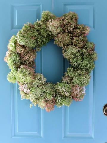 Beautiful hydrangea wreath on blue front door.