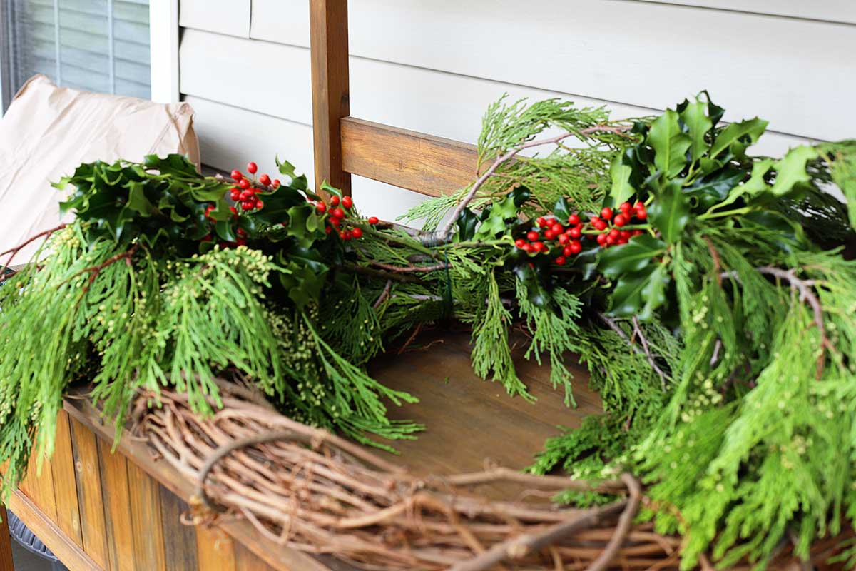 adding holly to evergreen wreath