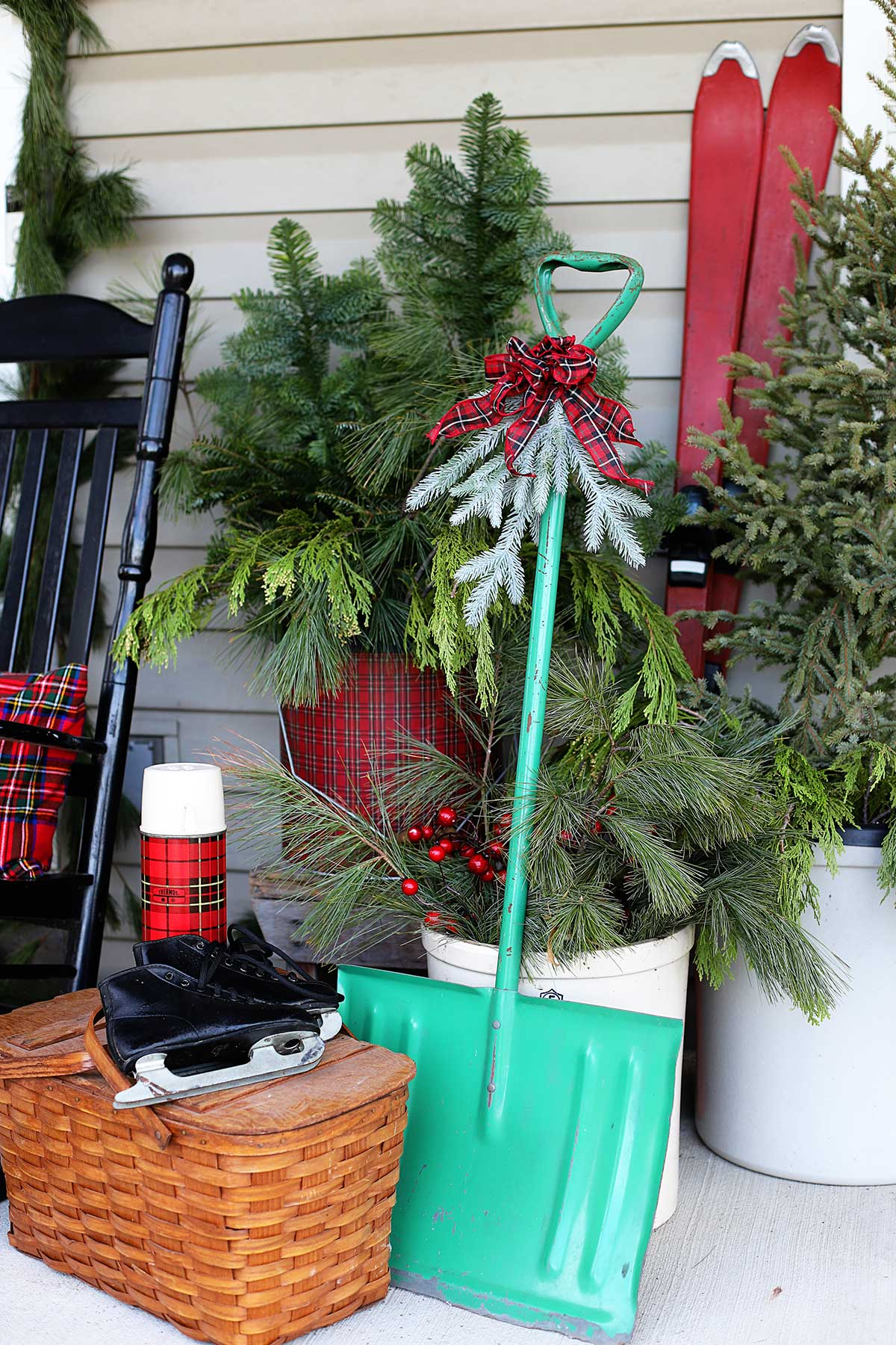 vintage skates, snow shovel and picnic basket on porch for Christmas decor
