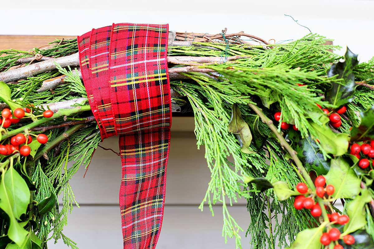 wrapping ribbon around evergreen wreath