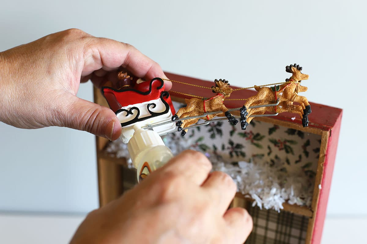 gluing santa sleigh for Christmas shadowbox
