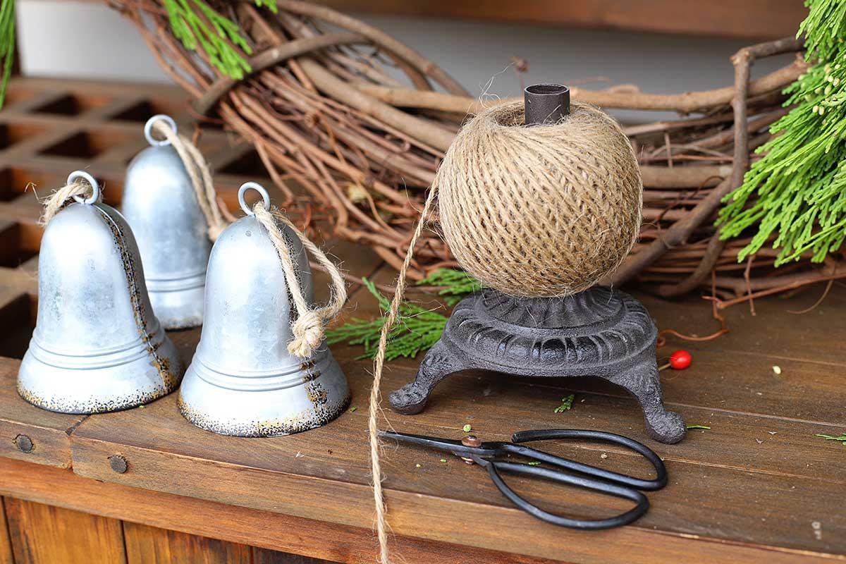 using twine to hang bells on wreath